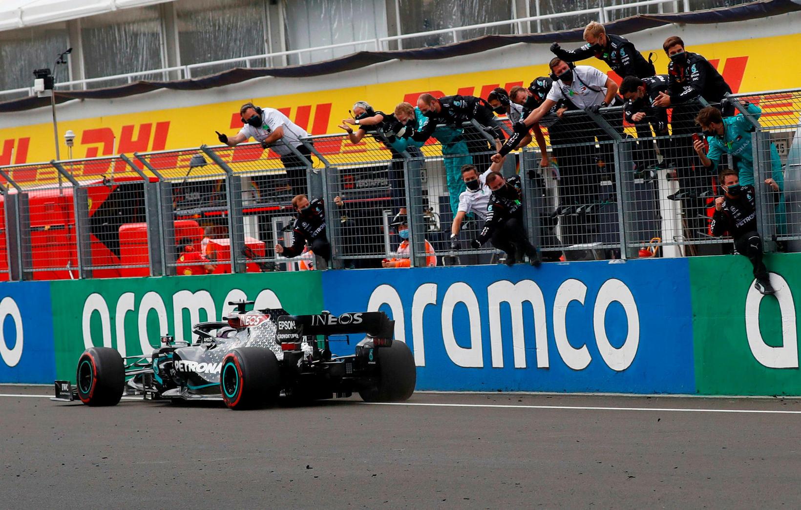 Liðsmenn Mercedes fagna Lewis Hamilton er hann ekur fyrstur allra …