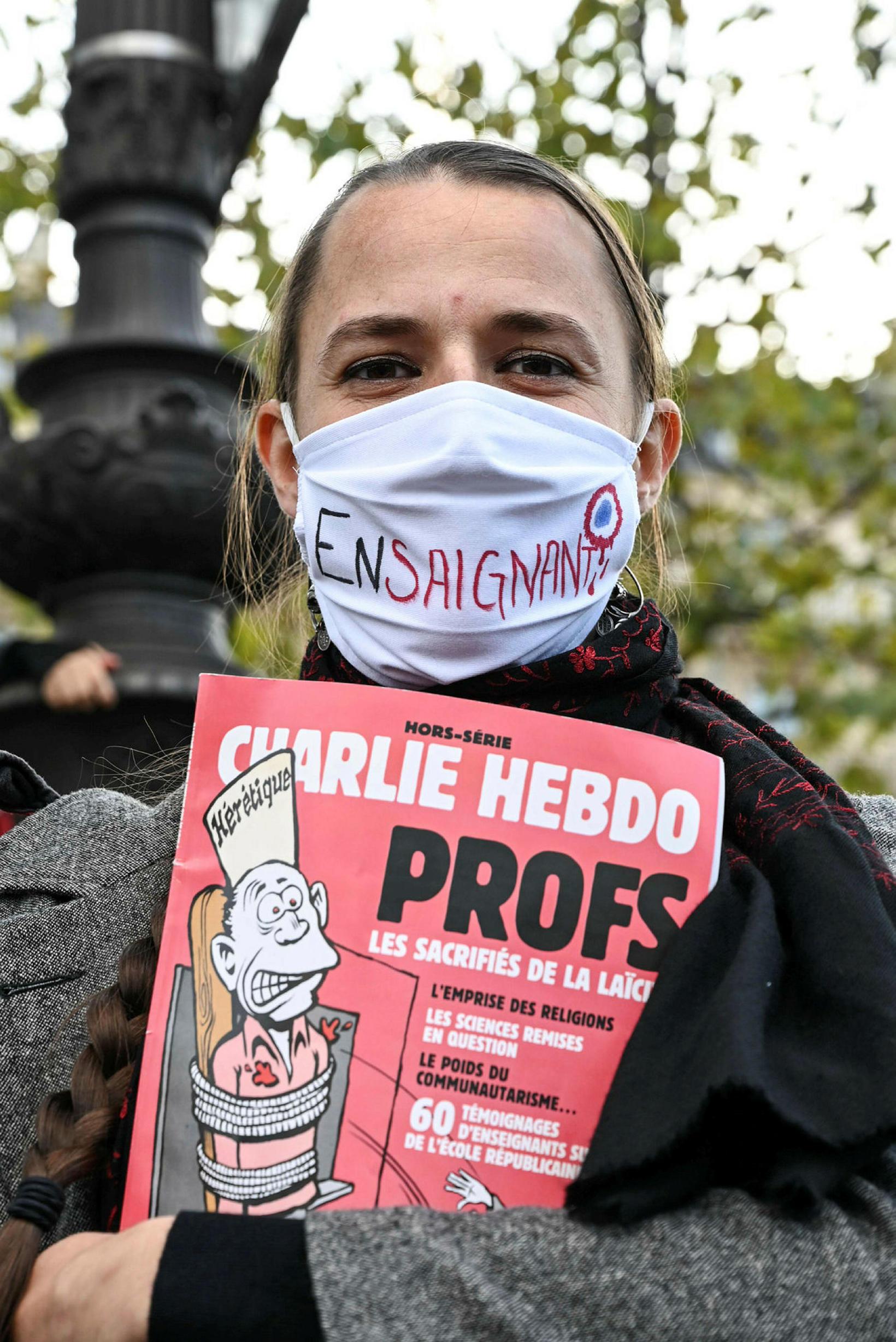 Kennari með eintak af Charlie Hebdo.