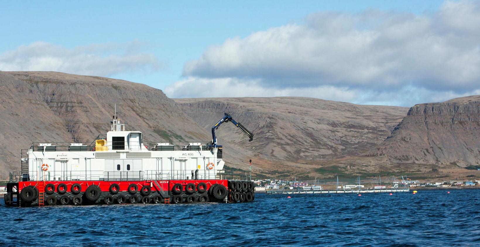 Einn af fóðurprömmum Arctic Fish við sjókvíar á Patreksfirði, skammt …