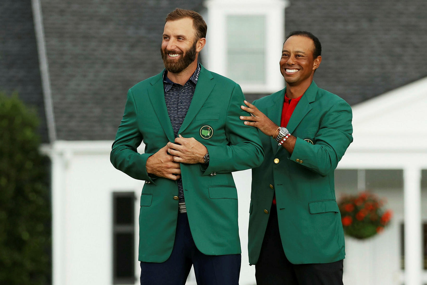 Tiger Woods klæðir Dustin Johnson í græna jakkann eftirsótta.