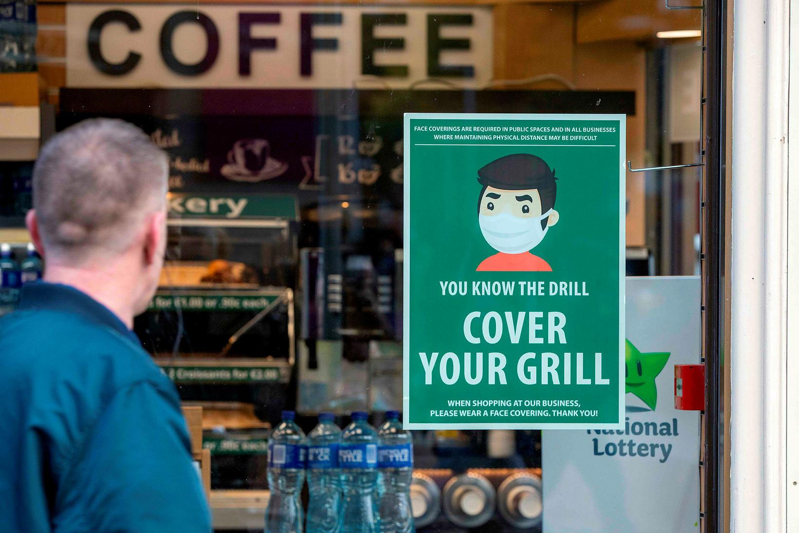 Maður horfir á plakat á kaffihúsi í Dublin.