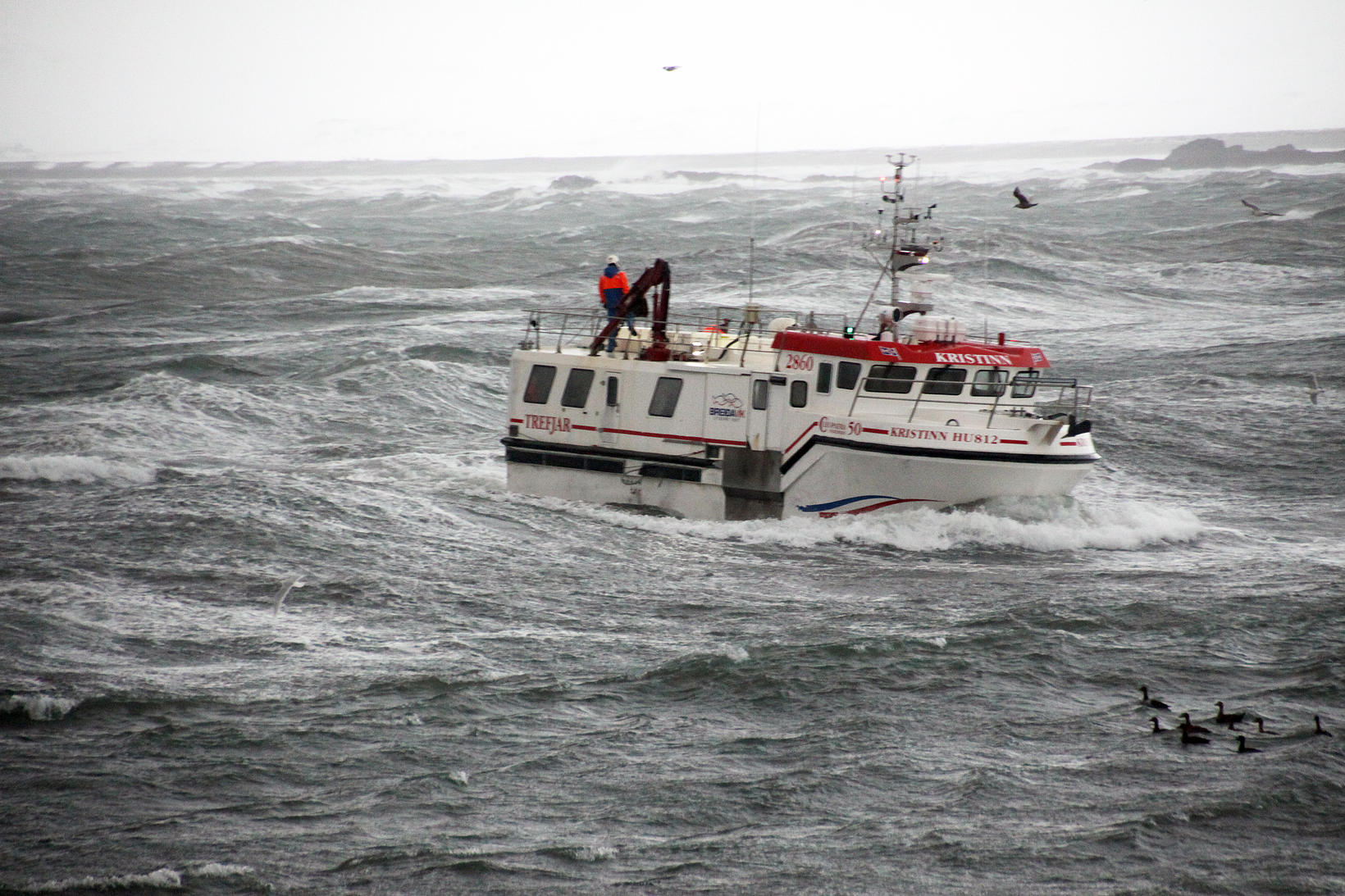 Kristinn HU að koma að landi í norðanbrælu.