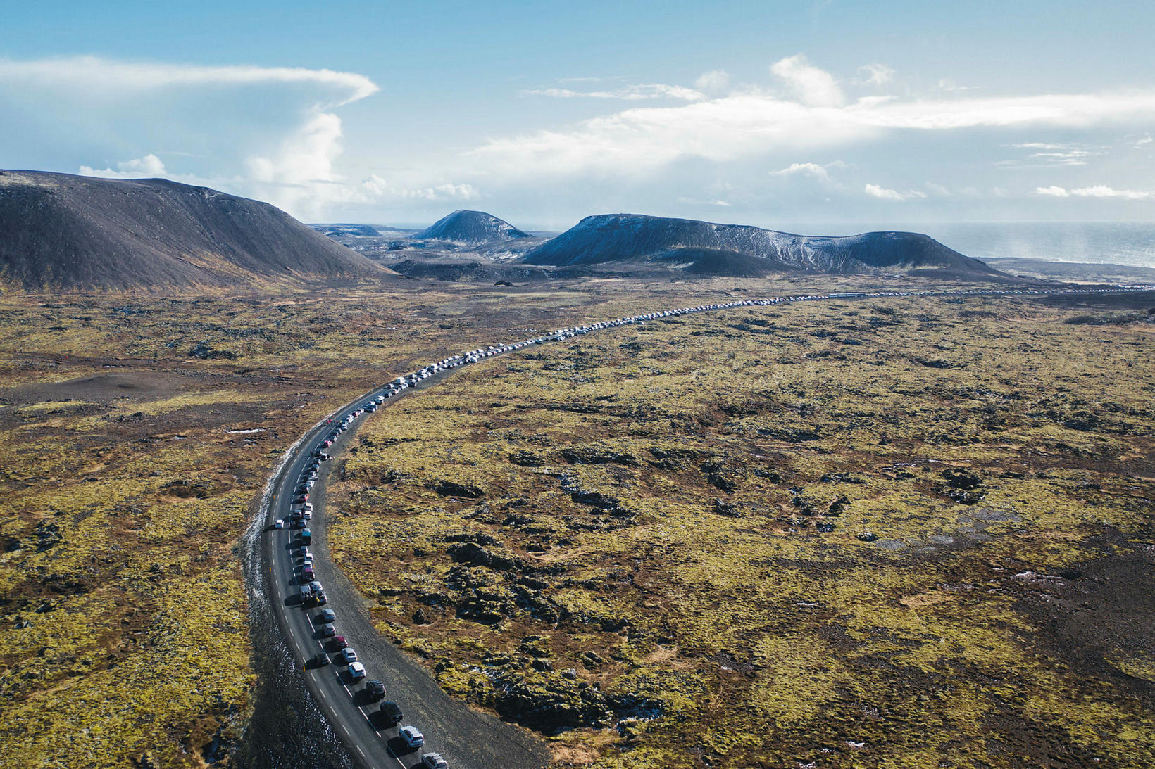 A long line of cars driving toward the eruption site …