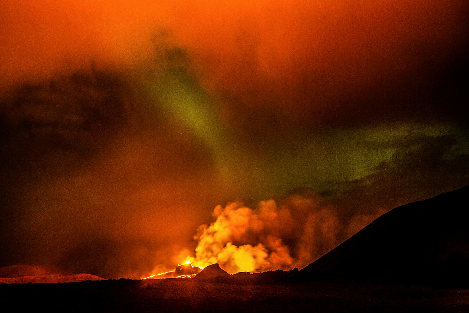The northern lights appear to rise from the volcano.