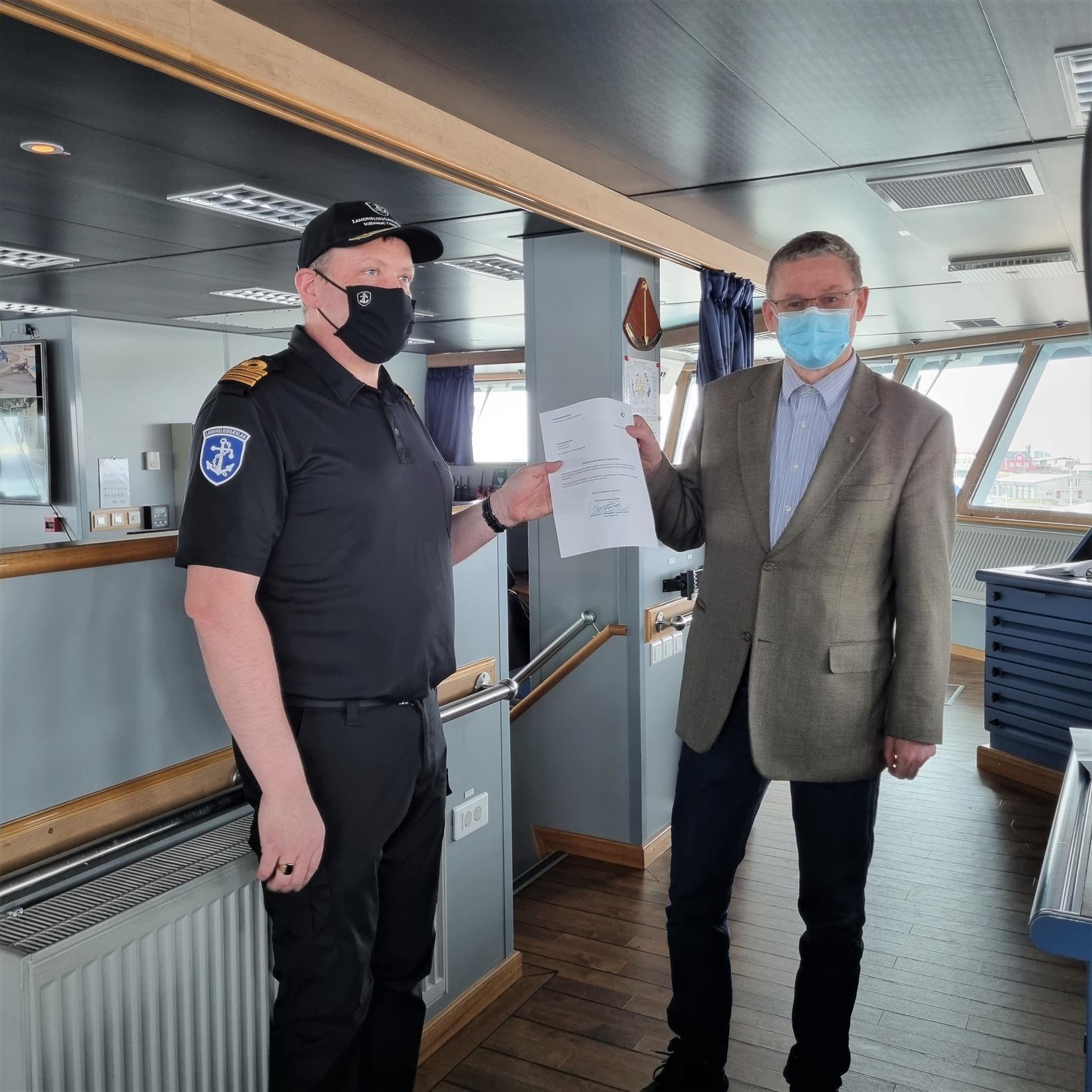 Jónas Egilsson hafnar- og sveitarstjóri, afhendir skipherranum Páli Geirdal skjal …