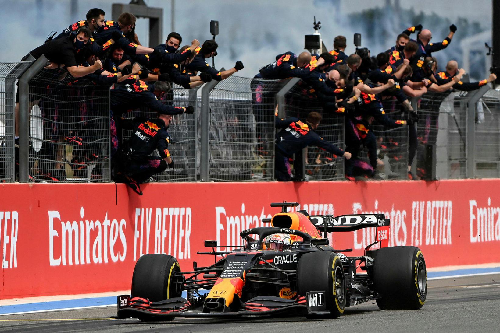 Liðsmenn Red Bull fagna Max Verstappen er hann ekur yfir …