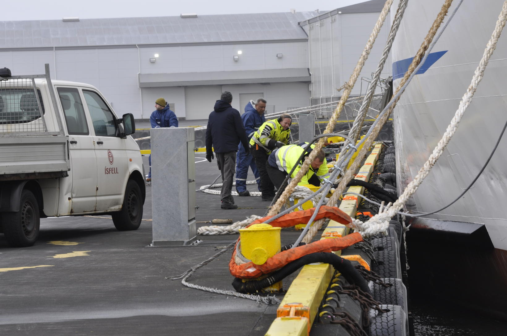 Workers tie the ship back to the dock.