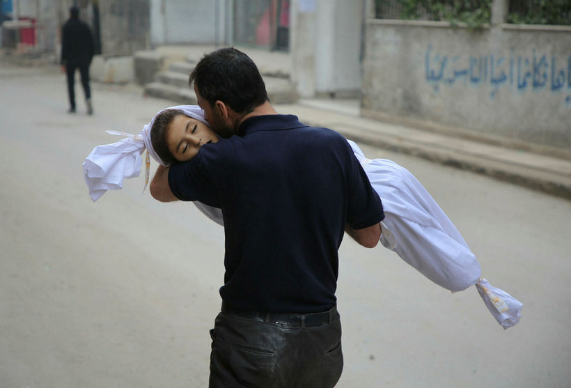 Faðir kyssir lík barns síns í bænum Zamalka í Ghouta.