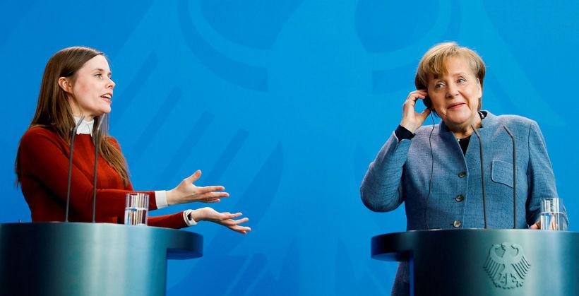 Katrín talar og Merkel hlustar á viðstöðulausa þýska þýðingu.