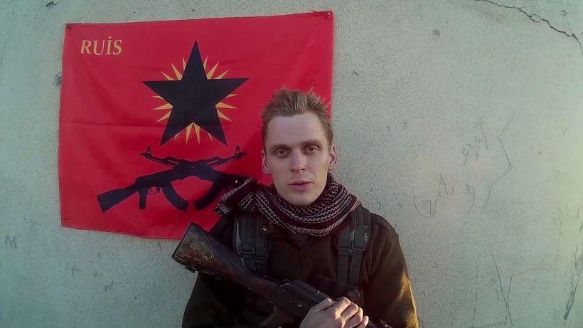 Skjáskot úr myndbandi gríska anarkistahópsins RUIS. Haukur stendur við fána ...