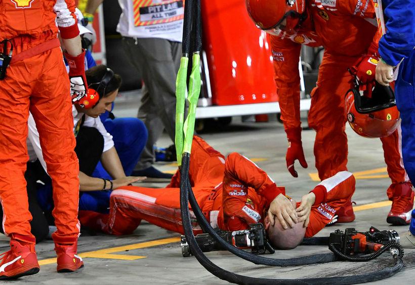 Liðsmaður Ferrari liggur á jörðinni eftir misheppnuð dekkjaskipti Kimi Räikkönen.