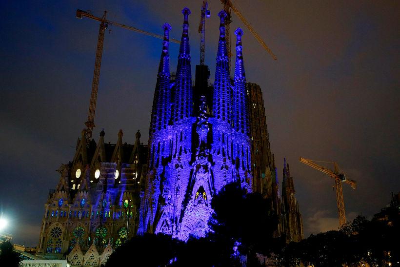 Sagrada Familia kirkjan í Barcelona lýst upp í bláum lit ...