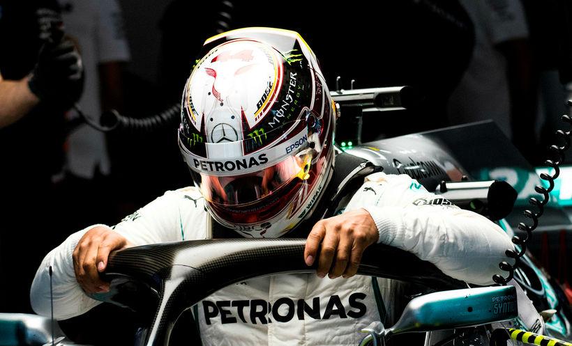 Lewis Hamilton smeygir sér niður í Mercedesbílinn á seinni æfingunni ...