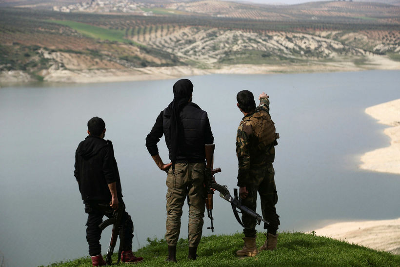 . Members of the armed Kurdish forces looking at lake ...