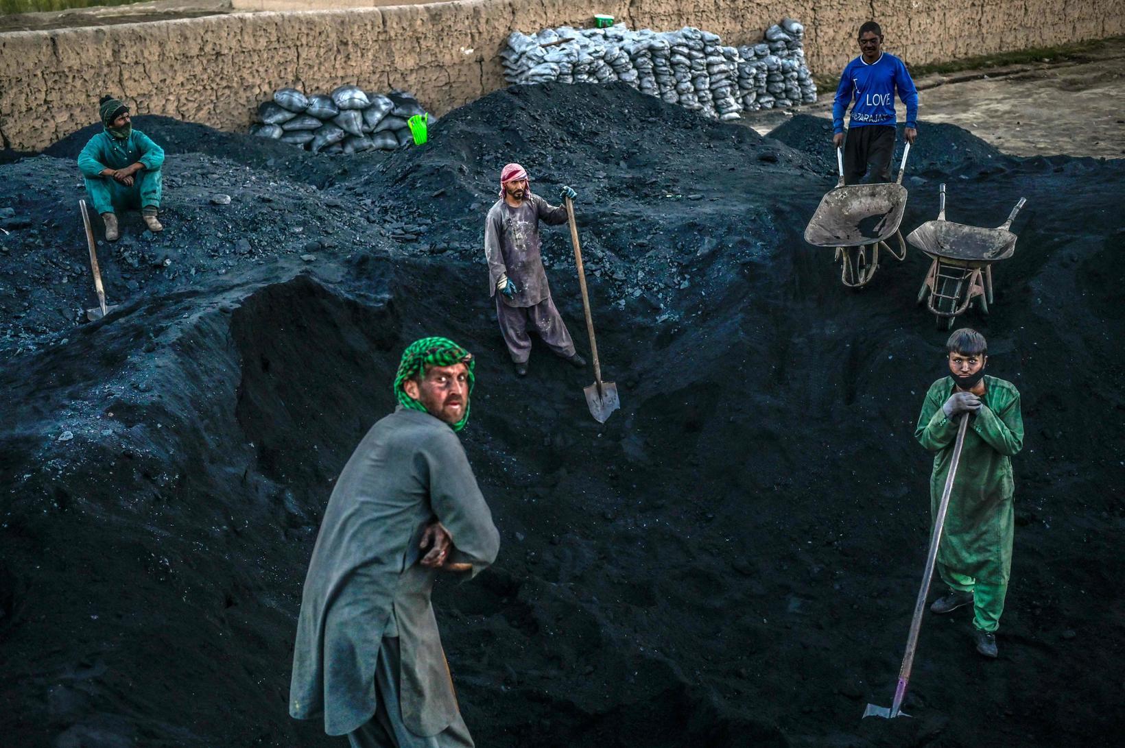 Verkamenn í Afganistan búa sig undir að moka kolum á …