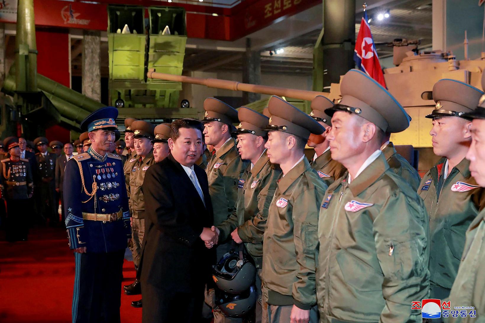 Kim Jong-un heilsar flugmönnum sem tóku þátt í hersýningunni.
