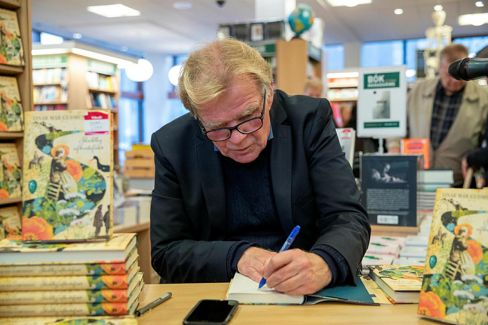 Einar Már Guðmundsson áritar bók sína.