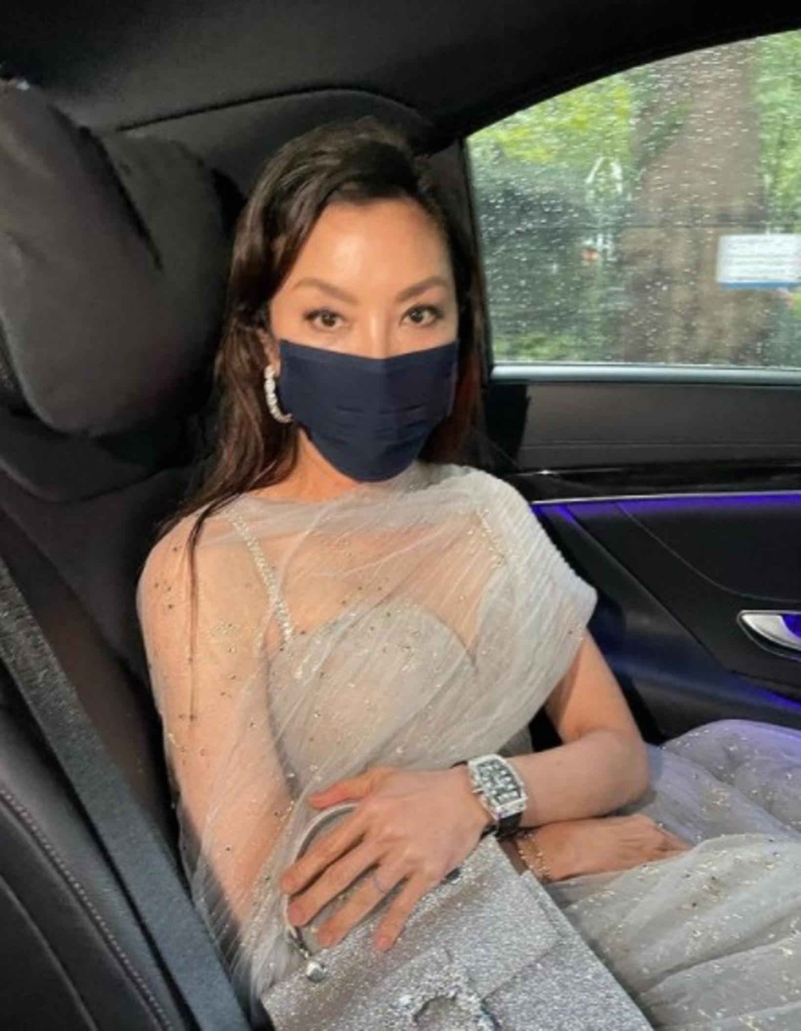 Michelle Yeoh á leið á frumsýningu með eyrnalokka og grímu.