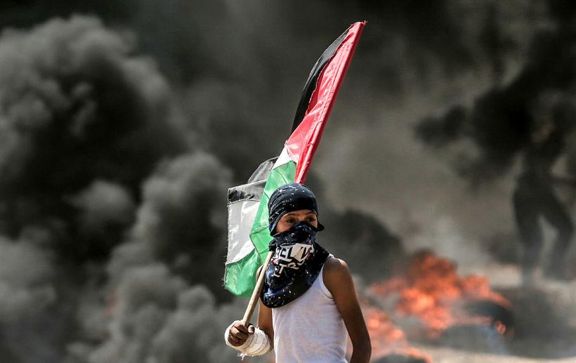 Palestínskur drengur heldur á þjóðfánanum á Gaza í dag.