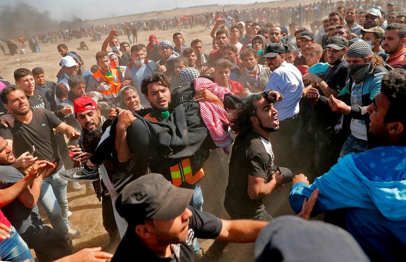 Palestínumenn halda á særðum mótmælenda á Gaza.
