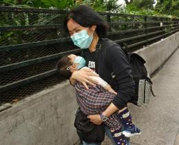 Kona og barn á götu í í Hong Kong.