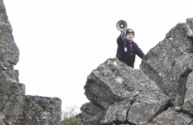 Þessi maður lét sírenuvæl glymja úr gjallarhorni sínu úr klettinum ...