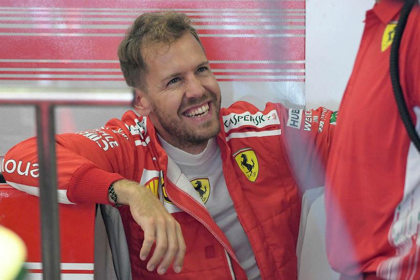 Sebastian Vettel slær á létta strengi við vélvirkja í bílskúr ...