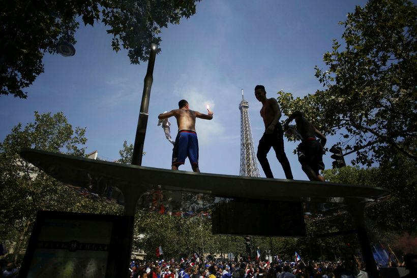 Stuðningsmenn Frakka standa á strætóskýli með Eiffelturninn í bakgrunni.