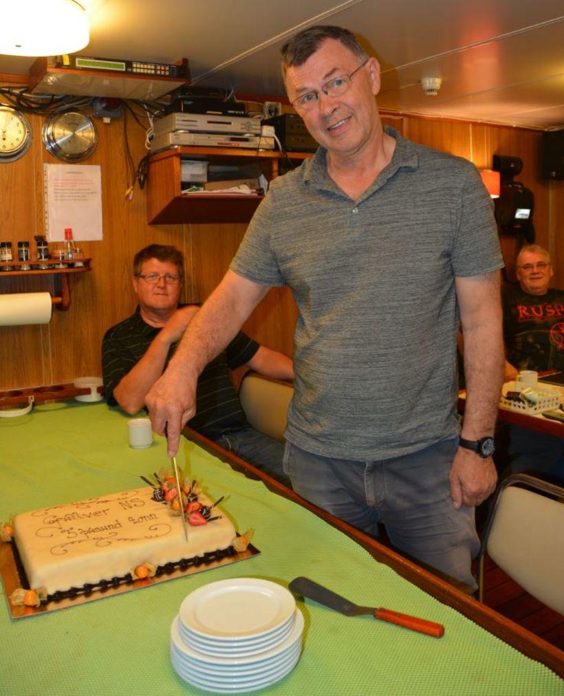 Rúnar L. Gunnarsson skipstjóri sker fimm þúsund tonna tertuna, sem ...