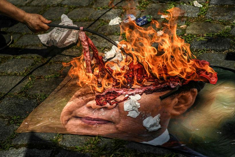 Stuðningsmenn uighur-múslima brenna hér mynd af Xi Jinping forseta Kína ...