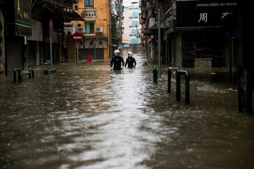 Björgunarmenn vaða flóðvatn í Macau.