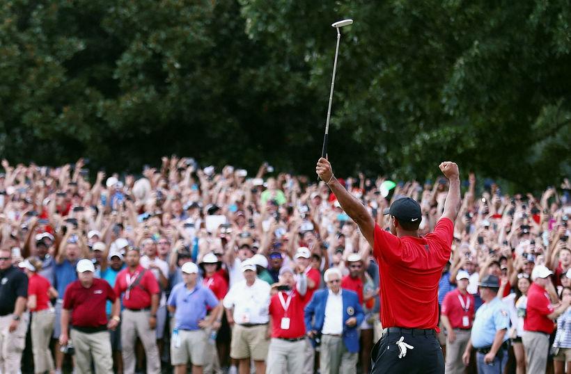 Tiger Woods fagnar sigri sínum eftir lokahöggið á 18. holunni.