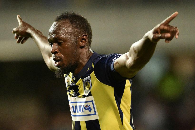 Usain Bolt fagnar marki.