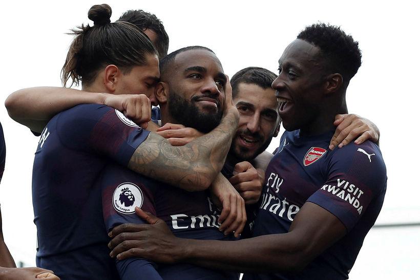 Alexandre Lacazette í faðmi vinnufélaganna hjá Arsenal.