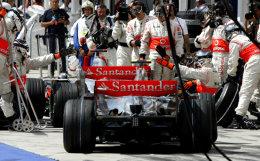 Hamilton bíður þess að Alonso aki af þjónustusvæðinu.