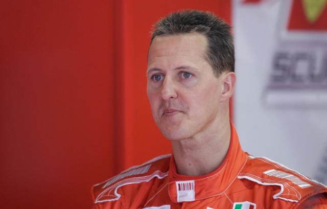Schumacher milli aksturslota í bílskúr Ferrari í Barcelona í dag.