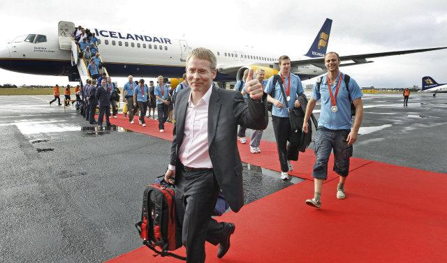 Landsliðsmennirnir ganga út úr flugvélinni á Reykjavíkurflugvelli.