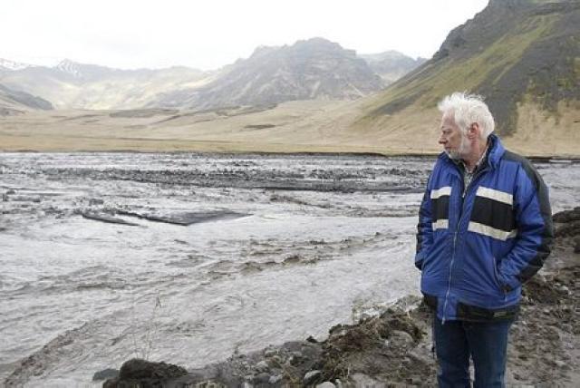 Ólafur Eggertsson, bóndi á Þorvaldseyri, virðir fyrir sér vatnsflaum í ...