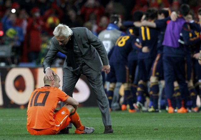 Bert van Marwijk hughreystir Wesley Sneijder á meðan Spánverjar fagna ...