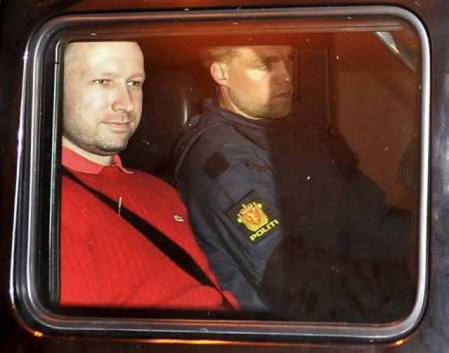 Anders Behring Breivik situr við hlið lögreglumanns í aftursæti bíls …