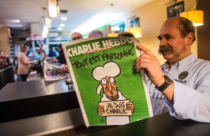 Franskur maður les fyrsta tölublað Charlie Hebdo sem britist eftir …