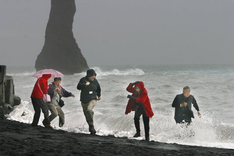 Tourists running from the waves at Reynisfjara.