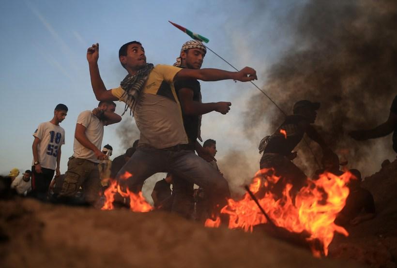 Palestínskur mótmælandi hendir steini í átt að lögreglu við Gaza.