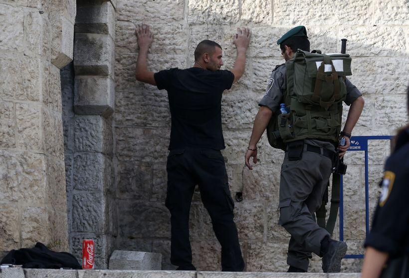 Lögreglumaður leitar á ungum Palestínumanni í Jerúsalem.