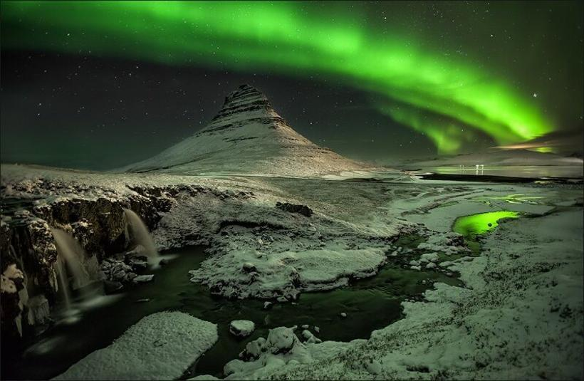 Mount Kirkjufell lit up by a starlit sky and the ...