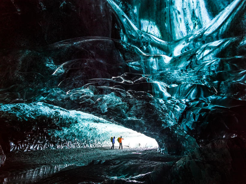 Climbers Klemen Premrl and Rahel Schelb inspect an ice cave ...