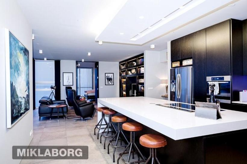 The kitchen features dark lacquered oak and bar-style kitchen table.