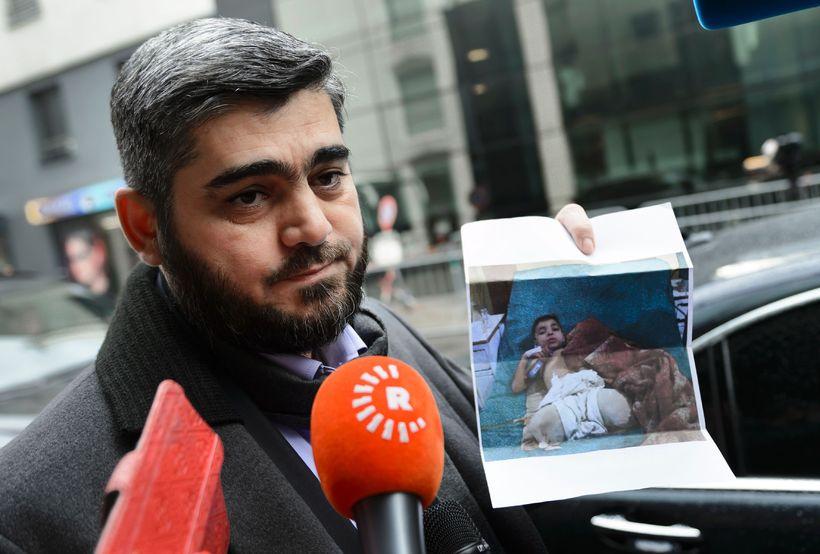 Mohammed Alloush heldur á mynd af dreng sem hann sagði ...