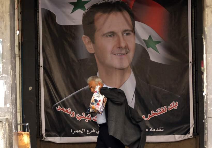 Sýrlenskur maður gengur framhjá mynd af Assad, forseta Sýrlands í ...