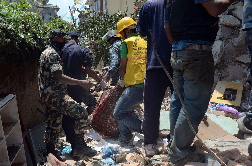 Nepalskir björgunarsveitarmenn grafa upp lík úr rústum húss í Katmandú ...